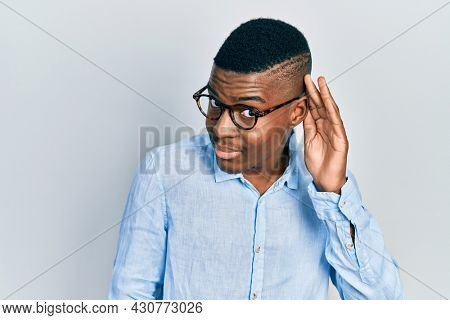 Young african american man wearing casual clothes and glasses smiling with hand over ear listening and hearing to rumor or gossip. deafness concept.