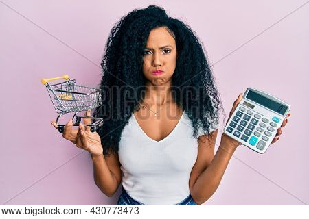 Middle age african american woman holding small supermarket shopping cart and calculator puffing cheeks with funny face. mouth inflated with air, catching air.