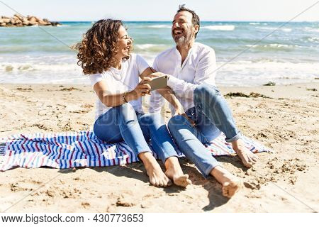 Middle age hispanic couple using smartphone sitting on the towel at the beach.