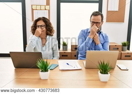 Middle age hispanic woman and man sitting with laptop at the office smelling something stinky and disgusting, intolerable smell, holding breath with fingers on nose. bad smell