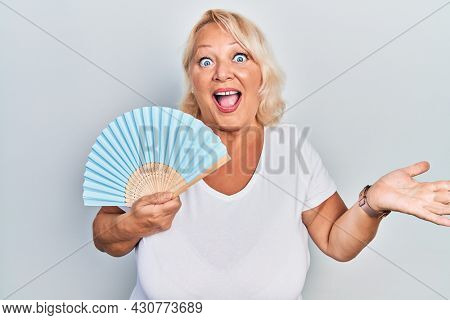 Middle age blonde woman waving hand fan cooling air in summer celebrating achievement with happy smile and winner expression with raised hand