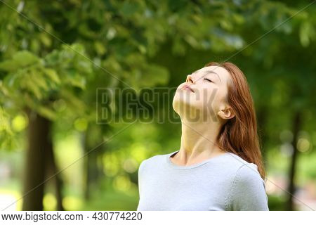Beautiful Woman Relaxing Breathing Fresh Air Standing In A Park