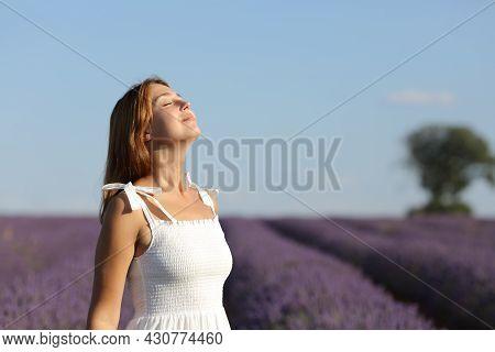 Happy Woman Wearing White Dress Breathing Fresh Air In Lavender Field