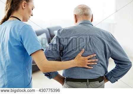 Doctor Or Nurse Caregiver With Senior Man At Home Or Nursing Home