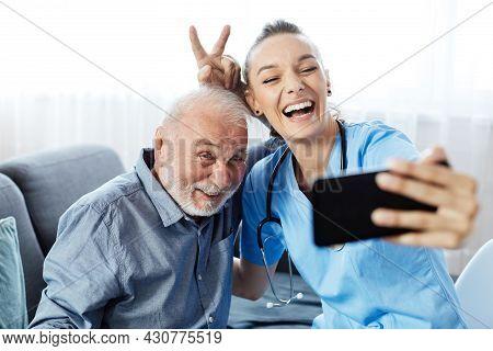 Doctor Or Nurse Caregiver Helping Senior Man With A Mobile Phone Taking Selfie At Home Or Nursing Ho