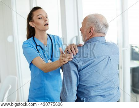 Doctor Or Nurse Caregiver Help Senior Man In Pain At Home Or Nursing Home