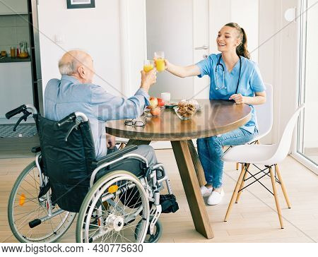 Doctor Or Nurse Caregiver With Senior Man In A Wheelchair At Home Or Nursing Home
