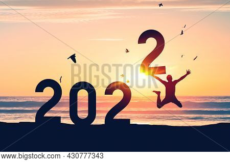 Silhouette Man Jumping And Holding Number 2 With Birds Flying On Sunset Sky At Tropical Beach And Nu