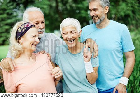 Smiling Active Senior People Posing Together In The Park