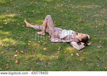 Young Woman Lies In The Park On The Grass With Closed Eyes - Digital Detox Concept.