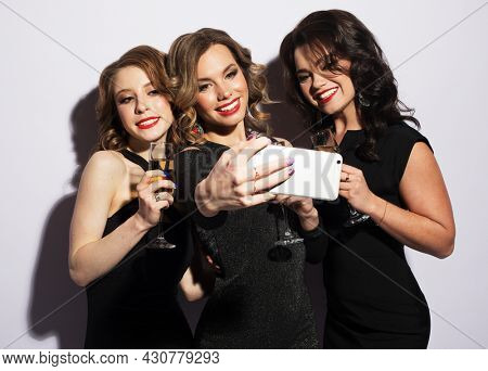 Three fashionable young women dressed in black cocktail dresses are singing with a microphone, holding disco balls, glasses of champagne and smiling