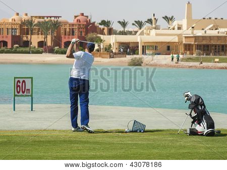 Male golfer training on a driving range poster