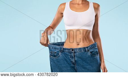 Close Up Of Woman Pulling Her Old Large Loose Jeans