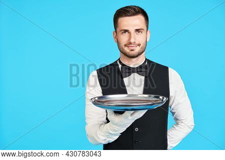 Attractive Young Waiter Holding Empty Silver Tray Over Blue Background