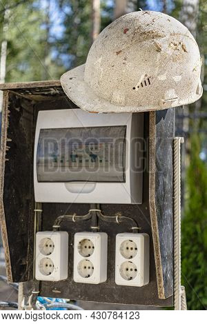 A Switchboard On A Construction Site With Sockets And An Old Work Helmet Hanging From It. Providing