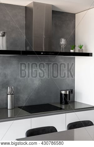Contemporary Clean Kitchen With Glossy Furniture, Countertop With Black Chairs Next To It, Black Ind
