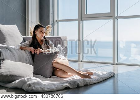 Young Sensual Woman Dressed In Homewear Sitting Near Sofa On Floor With Blanket And Many Decorative