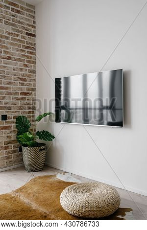 Vertical Picture Of Big Tv Screen On Clean White Wall In Modern Living Room With Straw Ottoman On Co
