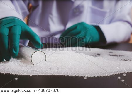 Man Hands Wearing Gloves Hold Polymer Pallet. Plastic Beads On Green Gloved Hand. Polymer Beads. The