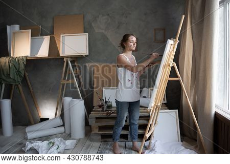 A Talented Artist Girl Draws A Picture On An Easel Canvas In An Art Workshop Or Drawing Studio. Crea
