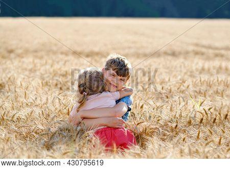 School Kid Boy And Little Sister, Preschool Girl Hugging On Wheat Field. Two Happy Children Playing