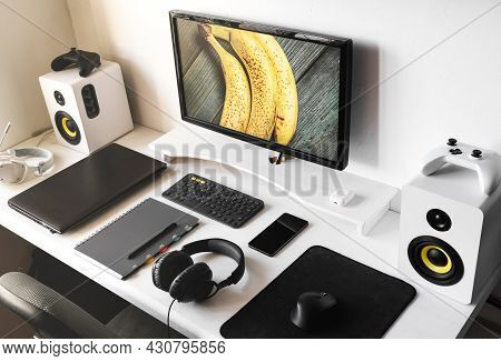 General View Comfortable Home Office Workplace Of Photographer With Computer, Camera Lens In Yellow-