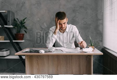 Burnout Syndrome At Work. Young Businessman In Stress At Workplace With Headache Unmotivated Works W
