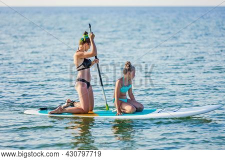 Mom And Daughter Float On The Water On The Board