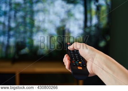 Woman Resting At Home. Person Watch Tv Set While Lying On The Sofa And Switch Channels With Remote C