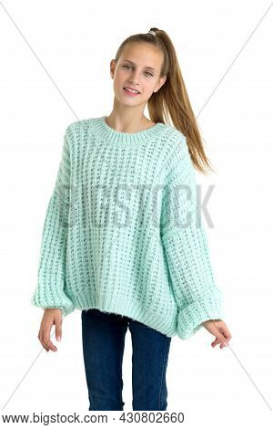 Pretty Stylish Teenage Girl In Trendy Outfit. A Teenage Girl With A Ponytail In A Warm Big Blue Swea