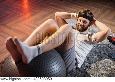 Middle Aged Ordinary Male Lying On Floor And Doing Exercises For Abdominal Muscles. Caucasian Bearde