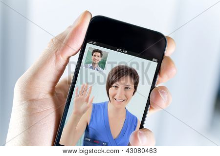 Closeup of a male hand holding an apple iphone during a video call with his girl field poster