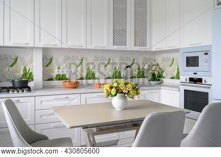 Modern compact white colored luxurious kitchen interior with dining table