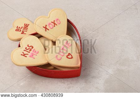 A heart shaped box overflowing with heart shapes sugar cookies with different sentiments written in icing.