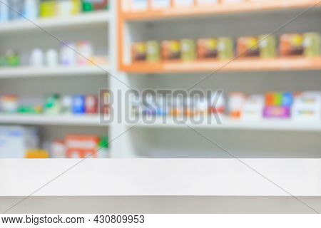 Blank White Pharmacy Table Counter With Blur Shelves Of Drug In The Pharmacy Drugstore Background, F