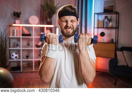 Middle Aged With Vivid Facial Expression Lifting Dumbbells During Evening Time At Home. Portrait Of