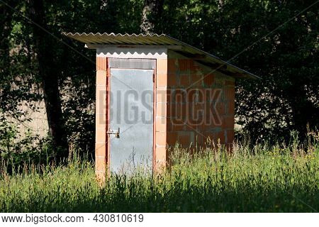 Unfinished Small Narrow Homemade Garden Tool Shed Made From Red Building Blocks And Closed With Meta