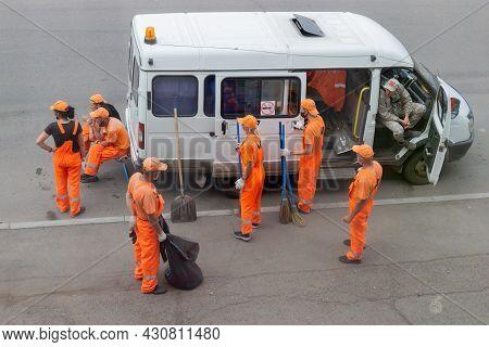 Krasnoyarsk, Russia - 19 August, 2021: Team Of Municipal Janitors In Orange Uniforms Resting After S