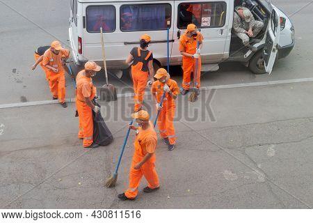 Krasnoyarsk, Russia - 19 August, 2021: Team Of Janitors In Orange Uniforms Sweeping The Street On Th