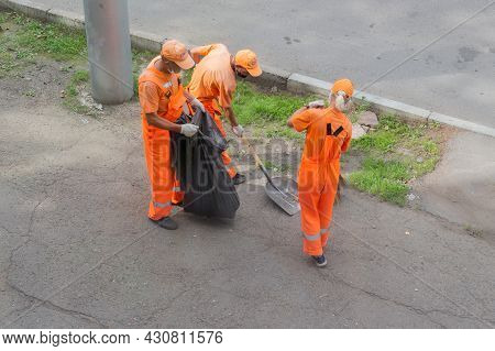 Krasnoyarsk, Russia - 19 August, 2021: Janitor Cleaners In Orange Uniforms With Scoops And Brooms Sw