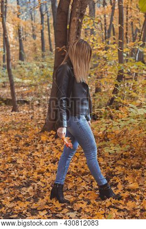 Lonely Sad Woman Is Kicking Yellow Leaves In Autumn. Sad Mood And Seasonal Affective Disorder Concep