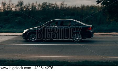 Fast Movig Opel Astra On The Road An Night. Poor Visibility At Night Concept. Side View Of Car With