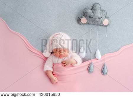 Cute newborn baby girl in knitted hat sleeping on grey stylized background with rainy cloud. Adorable infant child napping under pink blanket during studio photoshoot