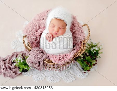Swaddled beautiful newborn baby girl sleeping in the basket with fur on light pink background. Cute female infant child photoshoot in studio. Adorable kid napping