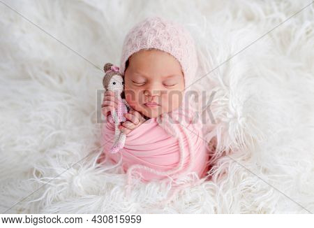 Swaddled beautiful newborn baby girl sleeping in white fur and holding knitted doll in her hands. Cute female infant child photoshoot in studio
