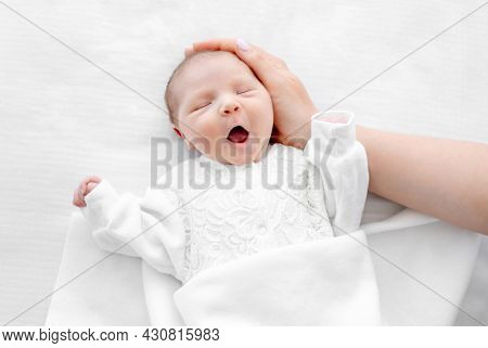 Adorable newborn baby girl wearing white costume lying in the bed at home with daylight, yawning during sleeping and her mother hand cares about her. Portrait of cute infant child and parent love