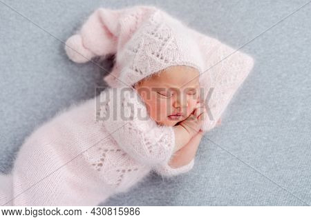 Cute newborn baby girl in knitted hat and costume sleeping on grey background and holding her hands under cheek. Adorable infant child napping during studio photoshoot. Little kid closeup portrait