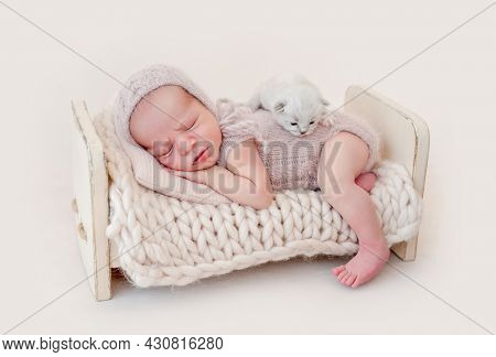 Adorable newborn baby boy sleeping on his tummy and little fluffy kitten lying on his back. Cute infant kid wearing knitted costume and hat napping with small cat kity during studio photoshoot