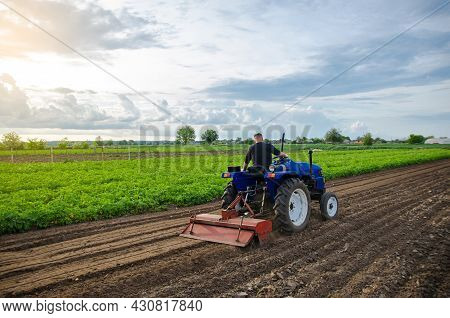 A Man Farmer Works In A Farm Field. Cultivating The Soil Before Planting A New Crop. Milling, Crushi