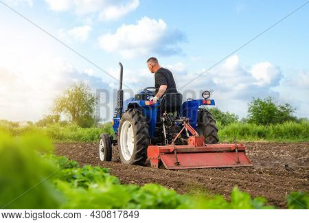 A Farmer On A Tractor Works In The Field. Milling Soil, Crushing And Loosening Ground. Working As A